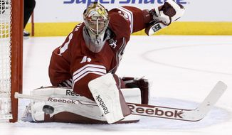Phoenix Coyotes' Mike Smith looks at the puck after it hit the post during the first period of an NHL hockey game against the Florida Panthers, Thursday, March 20, 2014, in Glendale, Ariz. (AP Photo/Ross D. Franklin)