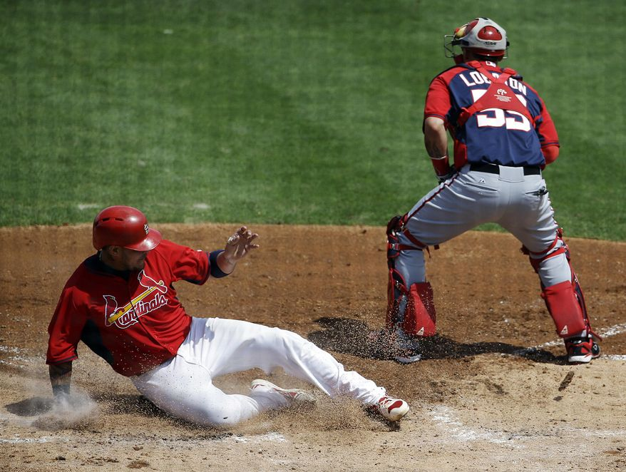 St. Louis Cardinals' Yadier Molina, left, scores off a sacrifice fly by teammate Allen Craig in the third inning of an exhibition spring training baseball game against the Washington Nationals, Friday, March 21, 2014, in Jupiter, Fla. (AP Photo/David Goldman)