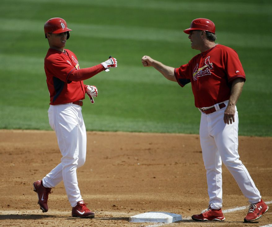 St. Louis Cardinals' Aledmys Diaz, left, fist-bumps first base coach Chris Maloney after hitting a single in the second inning of an exhibition spring training baseball game against the Washington Nationals, Friday, March 21, 2014, in Jupiter, Fla. (AP Photo/David Goldman)