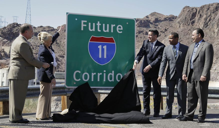 From left, Arizona Department of Transportation director John Halikowski, Arizona governor Jan Brewer, Nevada governor Brian Sandoval, Steven Horsford, D-Nev., and Nevada Department of Transportation director Rudy Malfabon unveil a sign that will mark the corridor for the future Interstate 11 between Phoenix and Las Vegas, Friday, March 21, 2014, at Hoover Dam, Ariz.  It was a symbolic effort meant to keep up momentum on the project, which is coming of age in an era of scarce highway funding. (AP Photo/Julie Jacobson)