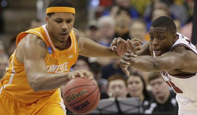 Tennessee forward Jarnell Stokes (5) vies for a loose ball against Massachusetts' Cady Lalanne during the first half of an NCAA college basketball second-round tournament game, Friday, March 21, 2014, in Raleigh, N.C. (AP Photo/Chuck Burton)