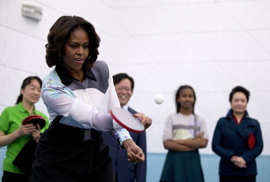 U.S. first lady Michelle Obama plays table tennis as Peng Liyuan, wife of Chinese President Xi Jinping, right, and others watch her during their visit to the Beijing Normal School, a school that prepares students to attend colleges overseas in Beijing, China Friday, March 21, 2014. (AP Photo/Andy Wong, Pool)