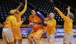 Tennessee center Mercedes Russell runs a gauntlet that includes head coach Holly Warlick, right, and assistant coach Dean Lockwood, second from right, during practice for an NCAA women's college basketball game Friday, March 21, 2014, in Knoxville, Tenn. Tennessee will face Northwestern State in a first-round playoff game Saturday. (AP Photo/Mark Humphrey)