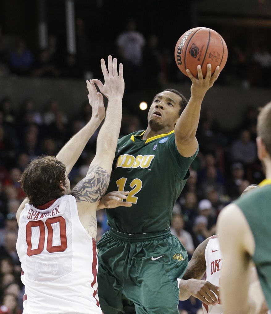 North Dakota State's Lawrence Alexander (12) shoots over Oklahoma's Ryan Spangler in the second half of a second-round game of the NCAA men's college basketball tournament in Spokane, Wash., Thursday, March 20, 2014. North Dakota State won in overtime, 80-75. (AP Photo/Elaine Thompson)