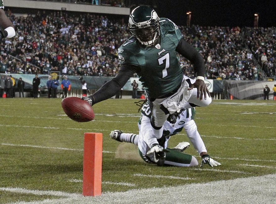 FILE - In a Dec. 18, 2011 file photo, Philadelphia Eagles quarterback Michael Vick (7) scores a touchdown in the first half of an NFL football game, in Philadelphia. The New York Jets signed quarterback Michael Vick and released Mark Sanchez on Friday, March 21, 2014. Vick was a free agent after spending the last five seasons with the Phialdelphia Eagles. (AP Photo/Matt Slocum, File)
