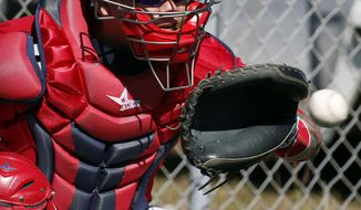 ADVANCE FOR WEEKEND EDITIONS, MARCH 22-23 - FILE - In this Feb. 17, 2014, file photo, Washington Nationals catcher Jose Lobaton catches the ball during a spring training baseball workout,in Viera, Fla. In a sabermetric age where everything is measurable, teams can calculate how many runs a catcher can save by mastering the art of pitch framing. This spring training, nationals general manager Mike Rizzo Rizzo made a trade with the Tampa Bay Rays to acquire Lobaton, in part because Lobaton rated well in pitch-framing. (AP Photo/Alex Brandon, File)