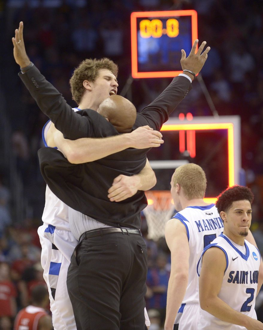 Saint Louis forward Rob Loe (51) hugs assistant coach Marcus Wilson after defeating North Carolina State 83-80 in overtime in a second-round game in the NCAA college basketball tournament Thursday, March 20, 2014, in Orlando, Fla. (AP Photo/Phelan M. Ebenhack)