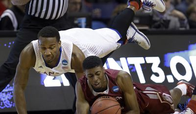 Eastern Kentucky's Marcus Lewis, right, and Kansas' Wayne Selden, Jr. dive after a loose ball during the first half of a second-round game in the NCAA college basketball tournament Friday, March 21, 2014, in St. Louis. (AP Photo/Jeff Roberson)