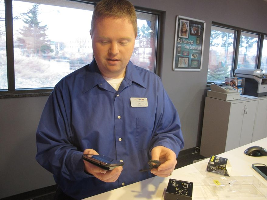 Wireless World Manager John Sterling, in the store in Pierre, S.D., hooks up a hands free device to his cell phone on March 21, 2014. He says a law banning texting while driving might increase sales of blue tooth devices.   A law that would make texting while driving illegal in South Dakota still awaits the governor's signature, but the state Department of Public Safety says it's already talking about a public awareness campaign. A state official says the state already has some materials to warn against texting and driving. He has been in touch with an ad agency in Sioux Falls to focus a campaign on the pending ban. The state spends about $1 million a year on safety campaigns including announcements that air on television. The ads target seat belt compliance and drunken driving.    (AP Photo/Nora Hertel)