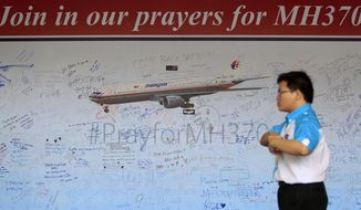 A man walks past a message board for passengers aboard a missing Malaysia Airlines plane, at a shopping mall in Petaling Jaya, near Kuala Lumpur, Malaysia, Friday, March 21, 2014. Planes are flying out of Australia again to search for two objects detected by satellite that may be debris from the missing Malaysian Airlines Flight 370. (AP Photo/Lai Seng Sin)