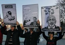 "Members of the Turkish Youth Union hold cartoons depicting Turkey's Prime Minister Recep Tayyip Erdogan during a protest against a ban on Twitter, in Ankara, Turkey, Friday, March 21, 2014. Turkey's attempt to block access to Twitter appeared to backfire on Friday with many tech-savvy users circumventing the ban and suspicions growing that the prime minister was using court orders to suppress corruption allegations against him and his government. Cartoon in center reads: Erdogan, left, to his Ankara Mayor Melih Gokcek "" we will rip out the roots of Twitter."" Gokcek: ""don't say it.""(AP Photo/Burhan Ozbilici)"