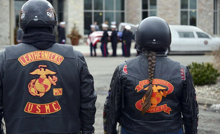 United States Marine Corps veteran Bob Lynch, left, with wife Sherrie, of Chatham, Ill., stand at attention as the flag-draped coffin of Capt. Reid Nannen is placed into a hearse following services at Eastview Christian Church in Bloomington, Ill., Saturday, March 22, 2014. Nannen, of Hopedale, Ill., died March 1 when his jet crashed during a training exercise in Nevada.  (AP Photo/The Pantagraph, Steve Smedley)