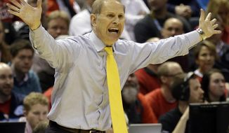Michigan head coach John Beilein directs his team during the first half of a third-round game against the Texas of the NCAA college basketball tournament Saturday, March 22, 2014, in Milwaukee. (AP Photo/Jeffrey Phelps)