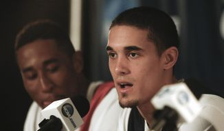Arizona guard Nick Johnson, flanked  by forward Rondae Hollis-Jefferson, talks about the teams' upcoming third round game against Gonzaga in the NCAA college basketball tournament at a news conference, Saturday, March 22, 2014, in San Diego. The teams play Sunday.  (AP Photo/Lenny Ignelzi)