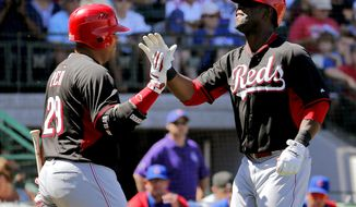 Cincinnati Reds' Roger Bernadina right, high-fives =Brayan Pena, left, after  Bernadina hit a three-run home run against the Chicago Cubs during the first inning of an exhibition spring training baseball game, Saturday, March 22, 2014, in Mesa, Ariz. (AP Photo/Matt York)