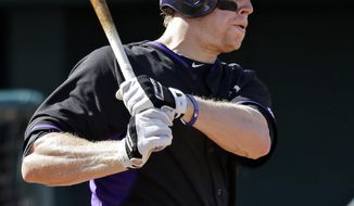 Colorado Rockies' Justin Morneau watches his bases-loaded, two-run single off Cleveland Indians starting pitcher Corey Kluber in the sixth inning of a spring exhibition baseball game Saturday, March 22, 2014, in Goodyear, Ariz. (AP Photo/Mark Duncan)