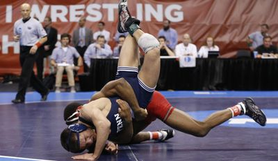 Cornell's Nashon Garrett, rear, wrestles Penn State's Nicholas Megaludis in a 125-pound match in the semifinals of the NCAA Division I wrestling championships in Oklahoma City, Friday, March 21, 2014. Garrett won the match. (AP Photo/Sue Ogrocki)