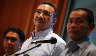 Malaysian Defense Minister Hishammuddin Hussein, center, Malaysia's Department of Civil Aviation director general Azharuddin Abdul Rahman, left, and Malaysia Airlines Group Chief Executive Ahmad Jauhari Yahya listen to a question of a journalist during a press conference at a hotel in Sepang, Malaysia, Saturday, March 22, 2014. Malaysia said Saturday that a Chinese satellite had spotted a large object along a broad stretch of ocean where officials hope to find a Malaysia Airlines plane that has been missing for more than two weeks. Hishammuddin told reporters Saturday that he had been informed that a Chinese satellite had spotted an object 22.5 meters (74 feet) by 13 meters (43 feet). (AP Photo/Joshua Paul)