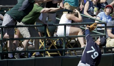 Seattle Mariners third baseman D.J. Peterson (79) catches a fould ball hit by Oakland Athletics' Daric Barton during the fourth inning of a spring exhibition baseball game in Phoenix, Saturday, March 22, 2014. (AP Photo/Chris Carlson)
