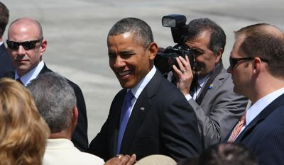 President Barack Obama is greeted upon his arrival at the Orlando International Airport in Orlando, Fla., Thursday, March 20, 2014, enroute to the Valencia Community College West campus to speak about the role of women in the U.S. economy. (AP Photo/Alex Menendez)