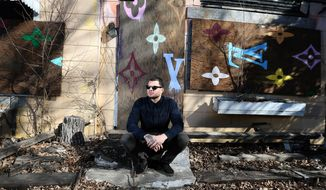 Des Moines artist Jordan Weber is photographed in front of a boarded up crack house on University Avenue in Des Moines, Iowa.  Weber doesn't call himself a street artist anymore. The term's overused. Overrated. Over-commodified, he says.  The 29-year-old is plotting a series of art installations that aim to turn abandoned buildings and lots in the urban core of Des Moines, where Weber grew up, into community green spaces. The first such project, an environmental art and garden concept plotted for River Bend, is in its early planning stages, he said. (AP Photo/The Des Moines Register, Bryon Houlgrave)  MAGS OUT, TV OUT, NO SALES, MANDATORY CREDIT