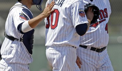 Minnesota Twins catcher Kurt Suzuki, left, pats starting pitcher Kevin Correia (30) on the back as he talks to pitching coach Rick Anderson, right, in the fourth inning of an exhibition baseball game against the New York Yankees in Fort Myers, Fla., Saturday, March 22, 2014. (AP Photo/Gerald Herbert)