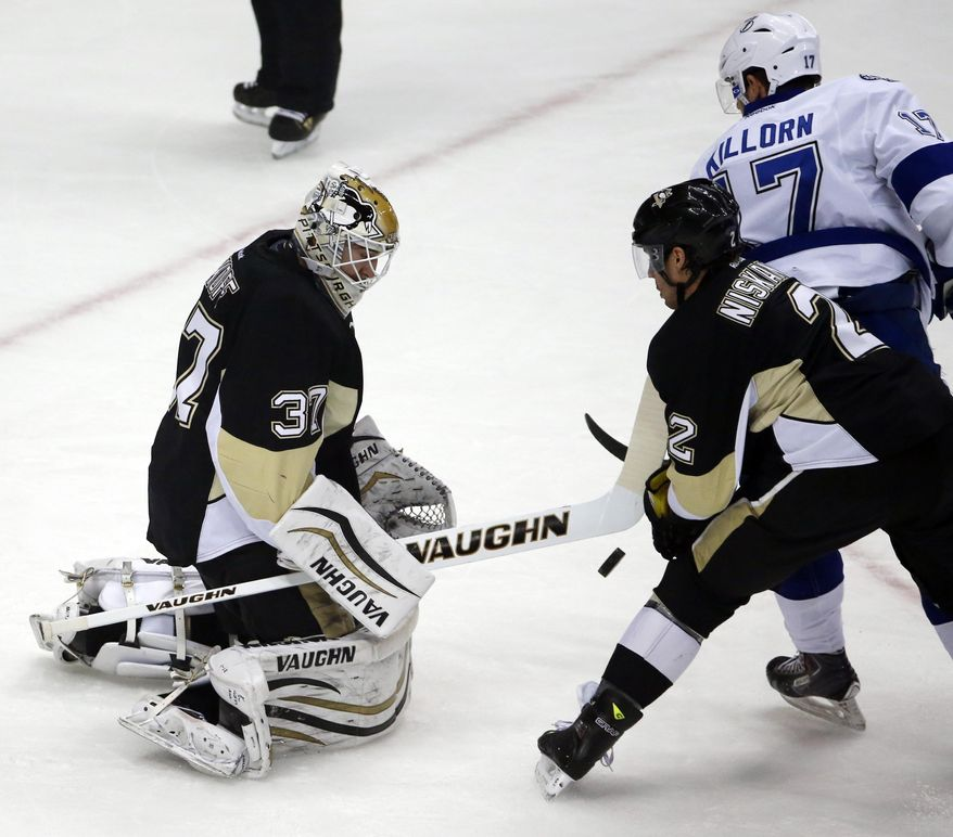 Pittsburgh Penguins goalie Jeff Zatkoff stops a shot by Tampa Bay Lightning's Alex Killorn (17) with the help of Matt Niskanen (2) in the first period of an NHL hockey game in Pittsburgh, Saturday, March 22, 2014. (AP Photo/Gene J. Puskar)