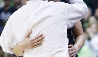 Robert Morris forward Artemis Spanou (15) is hugged by head coach Sal Buscaglia after coming out of the game in the second half against Notre Dame in a first-round game in the NCAA women's college basketball tournament, Saturday, March 22, 2014, in Toledo, Ohio. Notre Dame defeated Robert Morris 93-42. (AP Photo/Rick Osentoski)
