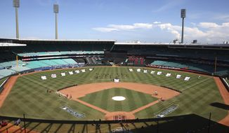 Pre-game entertainers rehears and ground crew put finishing touches on the field as preparations are made for the Major League Baseball opening game between the Los Angeles Dodgers and the Arizona Diamondbacks at the Sydney Cricket ground in Sydney, Saturday, March 22, 2014.  (AP Photo/Rick Rycroft)