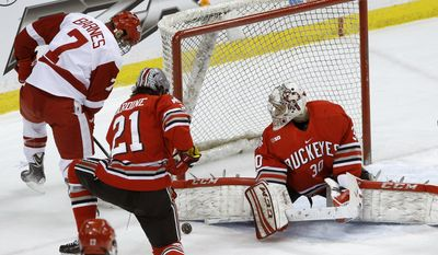 Ohio State goalie Christian Frey (30) deflects a shot by Wisconsin forward Tyler Barnes (7) in front of Ohio State defenseman Sam Jardine (21) during the first period of an NCAA college hockey game for the championship of the Big 10 Conference tournament in St. Paul, Minn., Saturday, March 22, 2014. (AP Photo/Ann Heisenfelt)