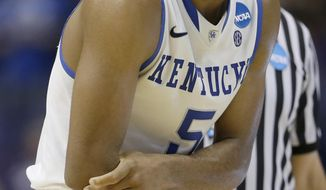 Kentucky's Andrew Harrison holds his arm as he walks to the bench during the second half of a second-round game  against Kansas State in the NCAA college basketball tournament, Friday, March 21, 2014, in St. Louis. Kentucky won the game 56-49. (AP Photo/Charlie Riedel)