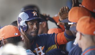 Houston Astros center fielder Dexter Fowler is congratulated in the dugout after scoring from third on a sacrifice fly by teammate Marc Krauss during the fourth inning of a spring exhibition baseball game in Kissimmee, Fla., Saturday, March 22, 2014. (AP Photo/Carlos Osorio)