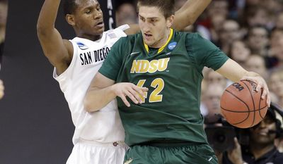 San Diego State's Skylar Spencer, left, defends against North Dakota State's Marshall Bjorklund in the first half during the third round of the NCAA men's college basketball tournament in Spokane, Wash., Saturday, March 22, 2014. (AP Photo/Elaine Thompson)
