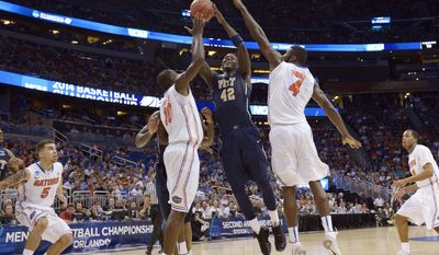 Pittsburgh forward Talib Zanna (42) shoots as Florida center Patric Young (4) and forward Dorian Finney-Smith (10) defend during the second half in a third-round game in the NCAA college basketball tournament  Saturday, March 22, 2014, in Orlando, Fla. (AP Photo/Phelan M. Ebenhack)