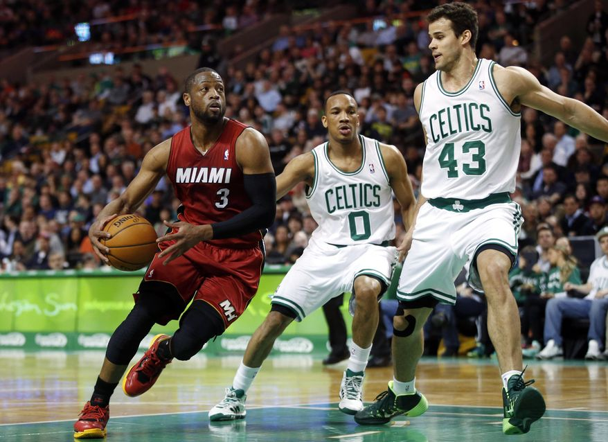 Miami Heat guard Dwyane Wade (3) drives against Boston Celtics guard Avery Bradley (0) and center Kris Humphries (43) in the first quarter of an NBA basketball game in Boston on Wednesday, March 19, 2014. (AP Photo/Elise Amendola)