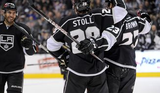 Los Angeles Kings left wing Dwight King, right, looks on as center Jarret Stoll (28) celebrates teammate Los Angeles Kings right wing Dustin Brown's, (23) goal during the second period of an NHL hockey game against the Florida Panthers, Saturday, March 22, 2014, in Los Angeles. (AP Photo/Gus Ruelas)