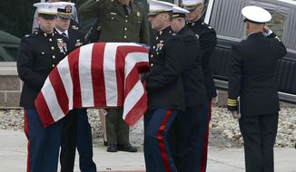 A United States Marine Corps honor guard places the flag-draped coffin of Capt. Reid Nannen into a hearse following services at Eastview Christian Church in Bloomington, Ill.,, Saturday, March 22, 2014. Nannen, of Hopedale, Ill., died March 1 when his jet crashed during a training exercise in Nevada. (AP Photo/The Pantagraph, Steve Smedley)