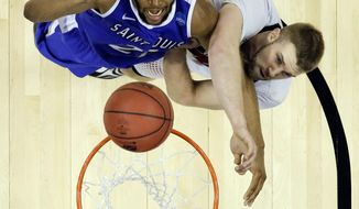 Saint Louis forward Dwayne Evans, left, and Louisville forward Stephan Van Treese, right, battle for a rebound during the second half of a third-round game in the NCAA college basketball tournament in Orlando, Fla., Saturday, March 22, 2014. (AP Photo/John Raoux)