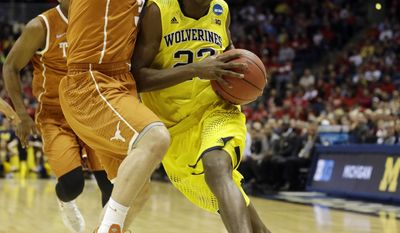 Michigan guard Caris LeVert (23) drives against Texas guard Javan Felix (3) during the first half of a third-round game of the NCAA college basketball tournament Saturday, March 22, 2014, in Milwaukee. (AP Photo/Morry Gash)