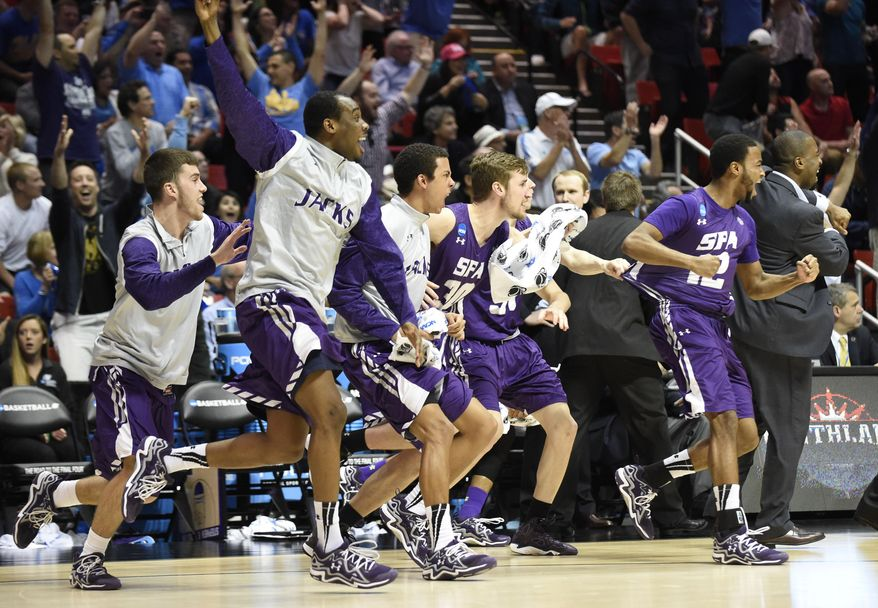 Stephen F. Austin players run on to the court as they beat Virginia Commonwealth 77-75 in overtime in a second-round game in the NCAA college basketball tournament Friday, March 21, 2014, in San Diego. nam (AP Photo/Denis Poroy)