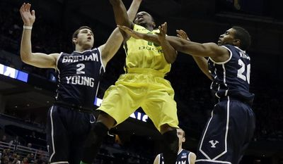 Oregon guard Johnathan Loyd (10) goes to the basket against BYU guards Matt Carlino (2) and Anson Winder (20) during the second half of a second-round game in the NCAA college basketball tournament Thursday, March 20, 2014, in Milwaukee. (AP Photo/Morry Gash)