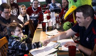 In this Tuesday, March 18, 2014 photo, Colin, 11, of Richland, Mich., shakes the hand of Kalamazoo Wings coach Nick Bootland after signing a contract to be a Kalamazoo Wing. The team presented Colin with a one-day contract that will allow him to join the Wings for their home game Sunday. Colin has a condition similar to Asperger's syndrome that makes it difficult to relate to peers. (AP Photo/Kalamazoo Gazette-MLive Media Group, Chuck Miller) ALL LOCAL TV OUT; LOCAL TV INTERNET OUT