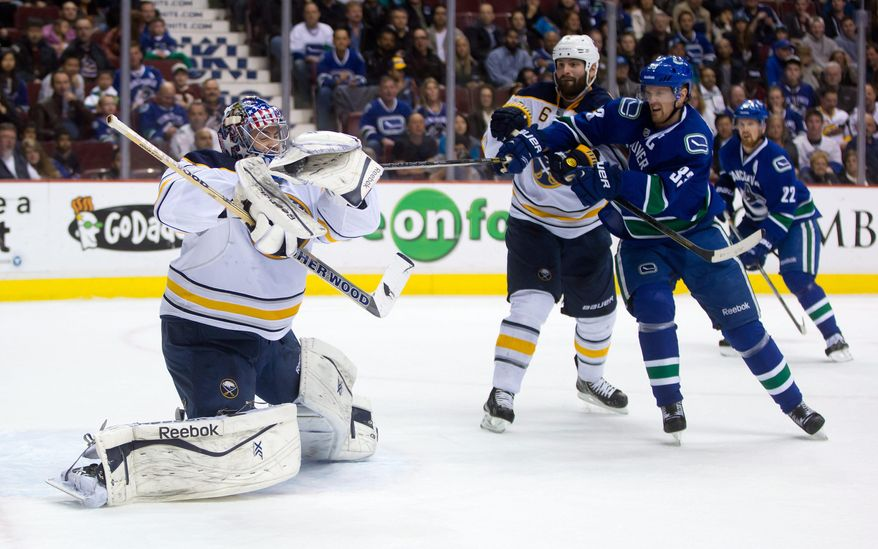 Buffalo Sabres' goalie Nathan Lieuwen, left, makes a glove save as Mike Weber, centre, defends while Vancouver Canucks' Henrik Sedin, of Sweden, looks for the rebound during first period NHL hockey action in Vancouver, British Columbia, on Sunday March 23, 2014. (AP Photo/The Canadian Press, Darryl Dyck)