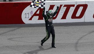 Kyle Busch (18) celebrates with the checkered flag after winning the NASCAR Sprint Series auto race in Fontana, Calif., Sunday, March 23, 2014. (AP Photo/Alex Gallardo)