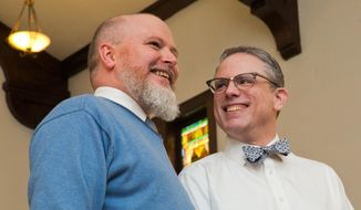 Corey Ledin-Bristol, left, and Art Ledin-Bristol smile during their wedding ceremony at the Harbor Unitarian Universalist church in Muskegon, Mich., on Saturday, March 22, 2014. (AP Photo/The Chronicle, Natalie Kolb)