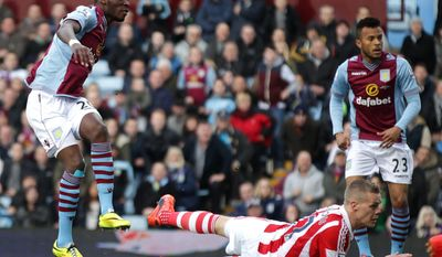 Aston Villa's Christian Benteke, left, scores his teams opening goal during their English Premier League soccer match against Stoke City at Villa Park, Birmingham, England, Sunday, March 23, 2014. (AP Photo/Nick Potts, PA Wire)    UNITED KINGDOM OUT    -    NO SALES   -   NO ARCHIVES
