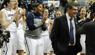 The Connecticut team sings Happy Birthday behind head coach Geno Auriemma, right, as he is interviewed on live television after their 87-44 win over Prairie View A&M in a first-round game of the NCAA women's college basketball tournament, Sunday, March 23, 2014, in Storrs, Conn. Today is Auriemma's 60th birthday. (AP Photo/Jessica Hill)