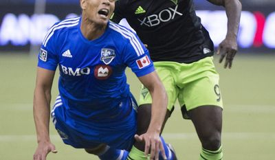Montreal Impact's Matteo Ferrari, left, is challenged by Seattle Sounders' Obafemi Martins for the ball during second half MLS soccer action in Montreal, Sunday, March 23, 2014.(AP Photo/The Canadian Press, Graham Hughes)