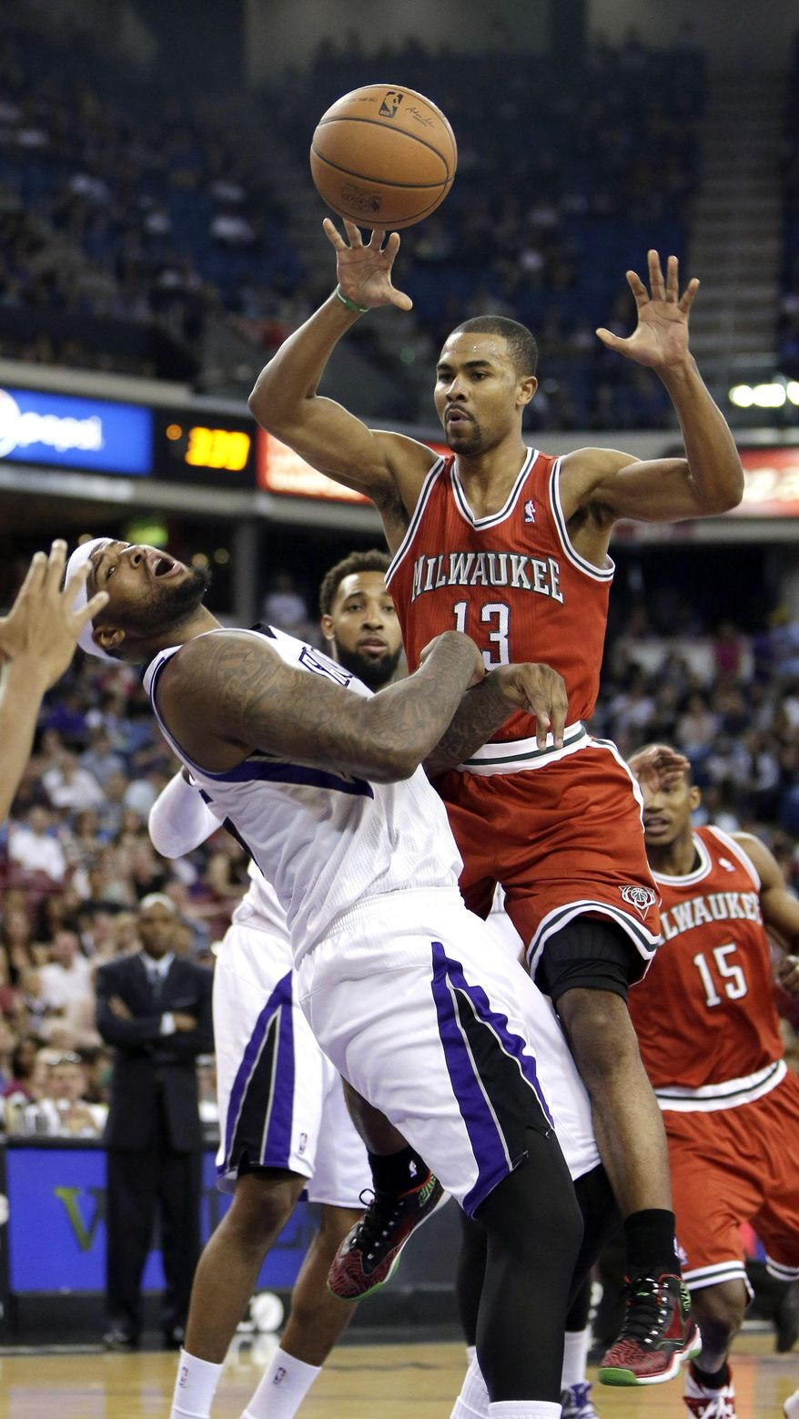 Sacramento Kings center DeMarcus Cousins, left, draws a charging foul against Milwaukee Bucks guard Ramon Sessions during the first quarter of an NBA basketball game in Sacramento, Calif., Sunday, March 23, 2014. (AP Photo/Rich Pedroncelli)