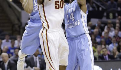 Iowa State's DeAndre Kane (50) is defended by North Carolina's J.P. Tokoto, left, and Desmond Hubert (14) during the first half of a third-round game in the NCAA college basketball tournament Sunday, March 23, 2014, in San Antonio. (AP Photo/Eric Gay)